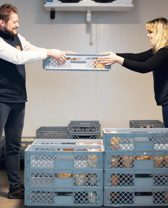 un homme et une femme tiennent un bac de produits melchior